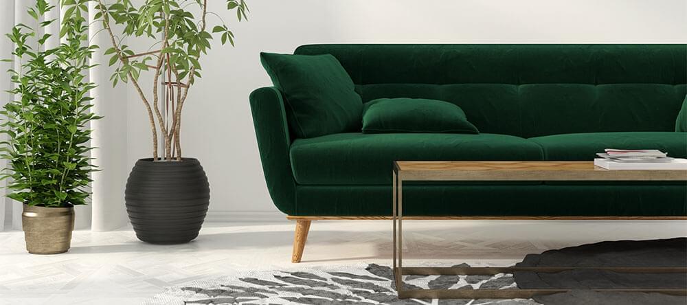 Ett mörkgrönt sammetsöverdrag för soffan kan kombineras väl med trä och mässing