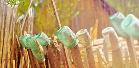 Leere Gläser auf einem Zaun